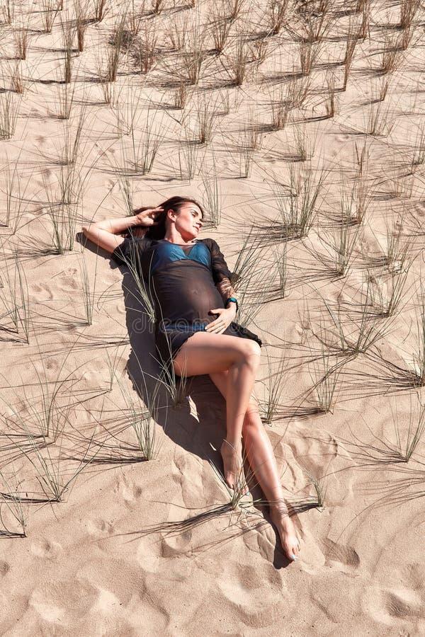 Het zwangere liggen op het zand en de struiken royalty-vrije stock foto's