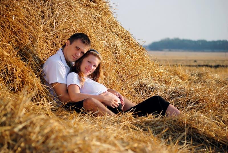 Het zwangere meisje en de kerel op maaien stock foto