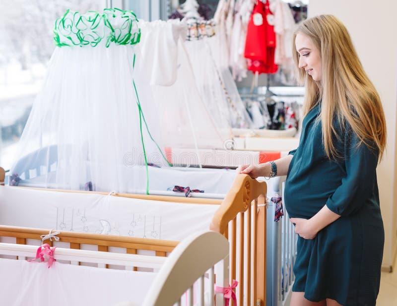 Het zwangere meisje kiest een babywieg in de opslag royalty-vrije stock foto