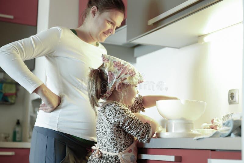 Het zwangere vrouw en meisje koken in de keuken stock fotografie