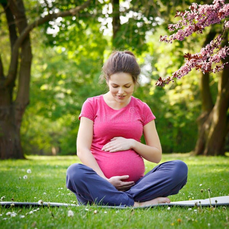 Het zwangere vrouw ontspannen in het de lentepark royalty-vrije stock foto