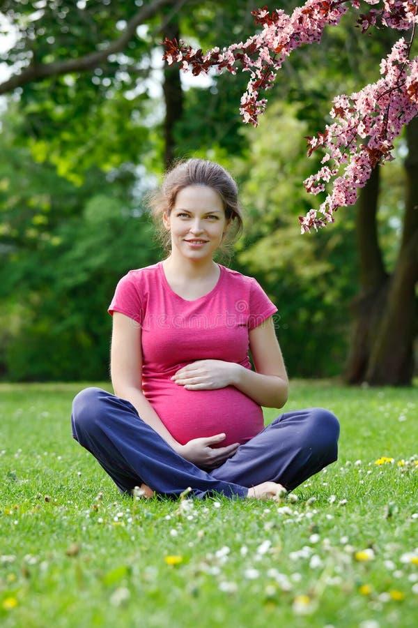 Het zwangere vrouw ontspannen in het de lentepark royalty-vrije stock fotografie