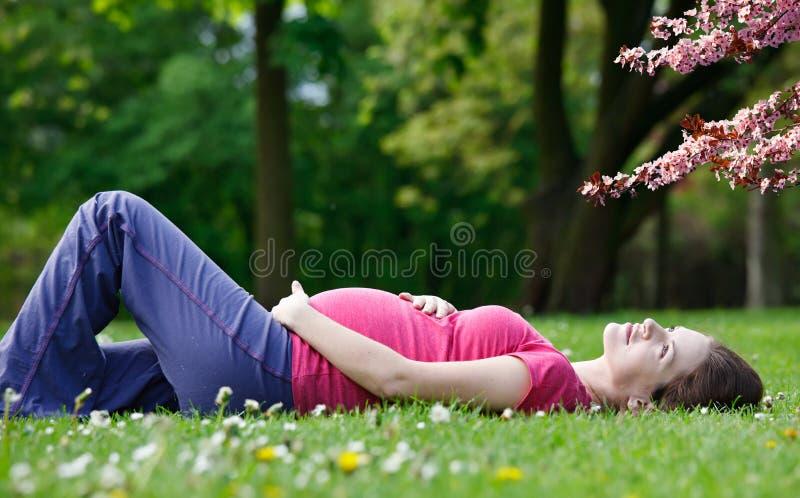 Het zwangere vrouw ontspannen in het de lentepark royalty-vrije stock foto's