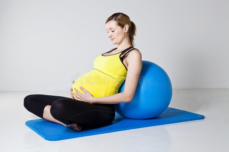 Het zwangere vrouw ontspannen tegen geschiktheidsbal royalty-vrije stock fotografie