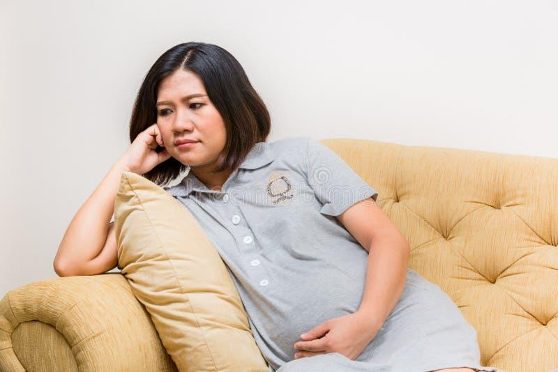 Het zwangere vrouw ontspannen thuis op bank royalty-vrije stock afbeeldingen