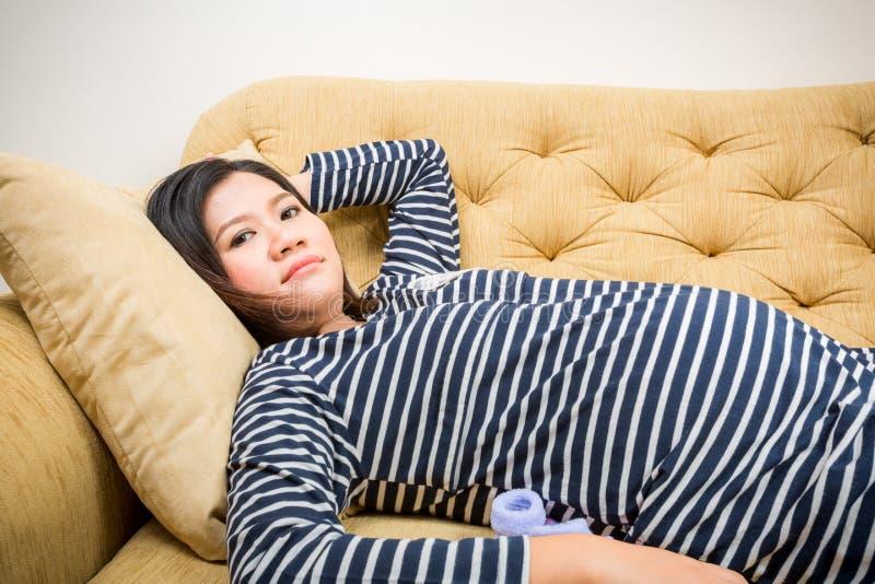 Het zwangere vrouw ontspannen thuis op bank stock afbeelding