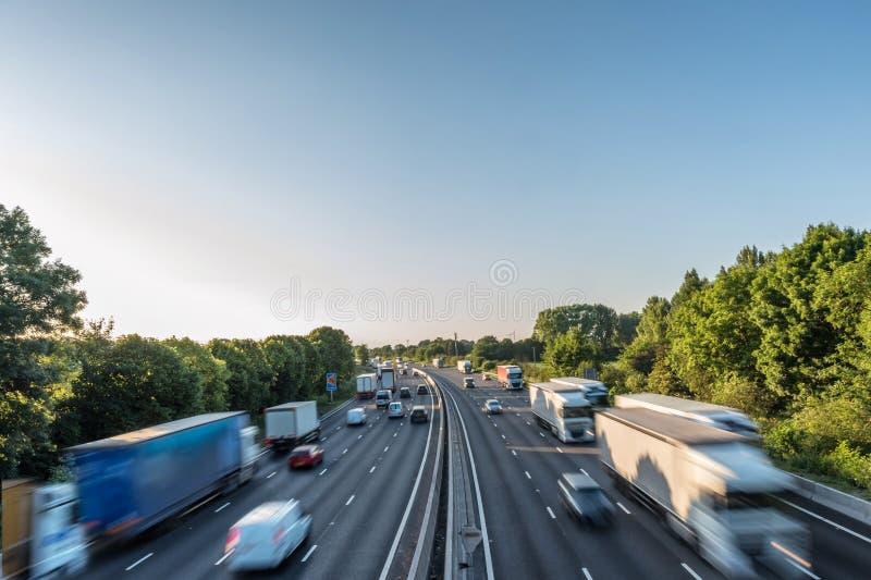 Het zware verkeer die van de zonsondergangmening zich bij snelheid op Britse autosnelweg in Engeland bewegen stock afbeeldingen