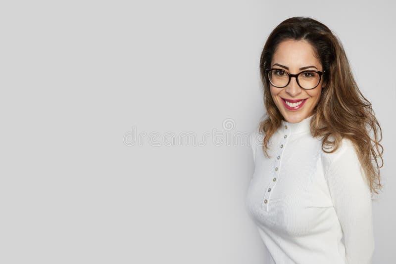 Het zwart-wit schot van gelukkige Kaukasische onderneemster met positieve glimlach, heeft kernachtig donker die haar, op witte mu royalty-vrije stock foto's