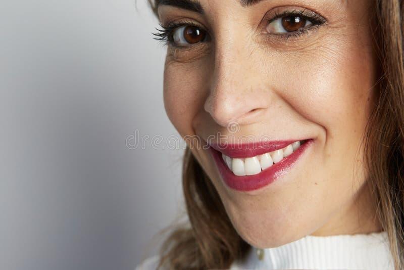 Het zwart-wit schot van gelukkige Kaukasische onderneemster met positieve glimlach, heeft kernachtig donker die haar, op witte mu royalty-vrije stock fotografie