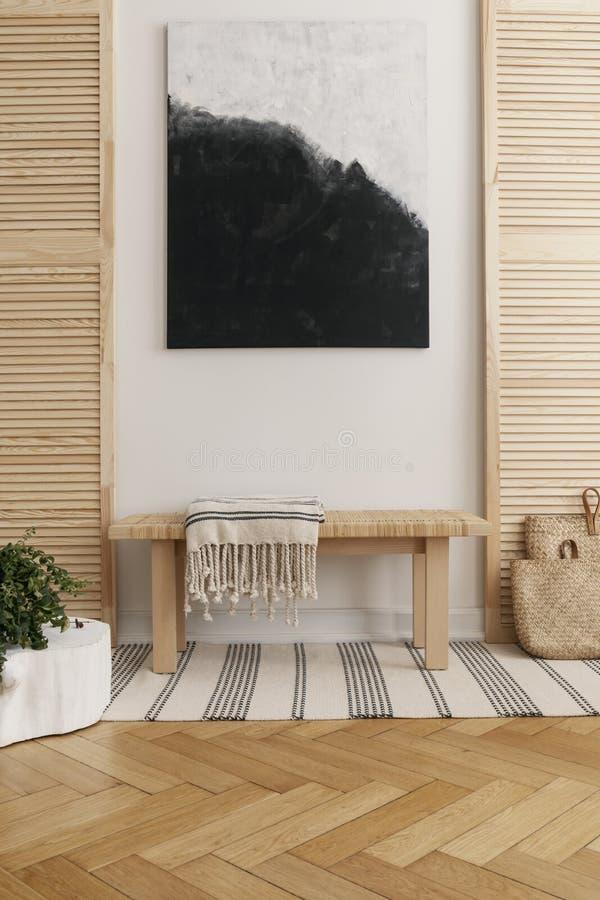 Het zwart-witte abstracte schilderen boven houten lijst in natuurlijk ontworpen binnenland stock afbeelding