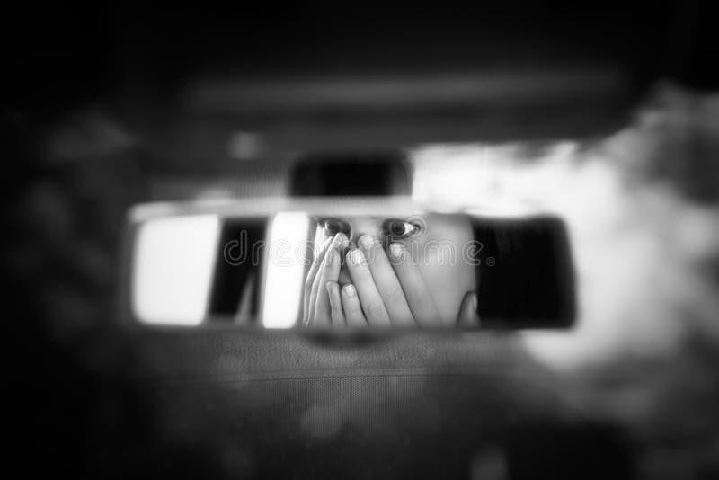 Het zwart-witte kunstbeeld van jonge vrouw met bang gemaakte ogen die haar gezicht behandelen met dient de autoachteruitkijkspieg royalty-vrije stock foto