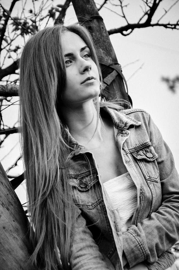 Het zwart-witte portret van zeker meisje met het broeden kijkt leunend op de boom stock fotografie