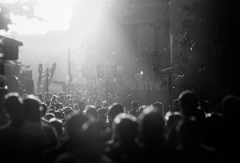 Het zwart-witte silhouet van mensen overbevolkt het lopen onderaan de voetstraat onder de zonneschijn royalty-vrije stock afbeeldingen