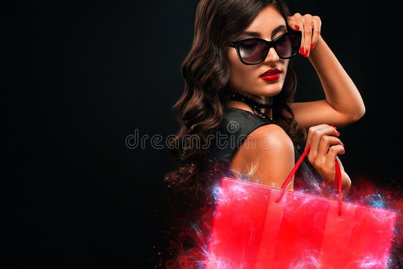 Het zwarte concept van de vrijdagverkoop Winkelende vrouw die rode die zak houden op donkere achtergrond in vakantie wordt ge?sol stock afbeelding