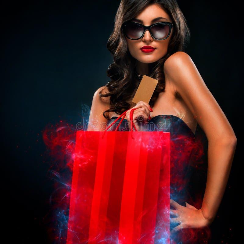 Het zwarte concept van de vrijdagverkoop Winkelende vrouw die rode die zak houden op donkere achtergrond in vakantie wordt ge?sol royalty-vrije stock foto