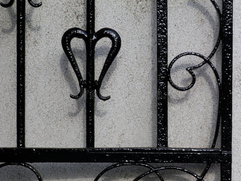 Het zwarte detail van de smeedijzerpoort tegen witte gipspleistermuur stock foto's