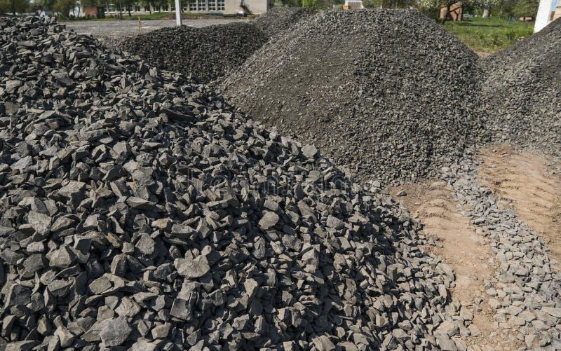 Het zwarte grint van wegstenen Rotsen voor bouw Verpletterd granietgrint, kleine rotsen stock foto