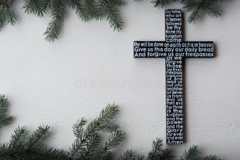 Het zwarte houten kruis met het gebed van Lord op de sjofele witte houten plank met spar vertakt zich achtergrond royalty-vrije stock afbeelding