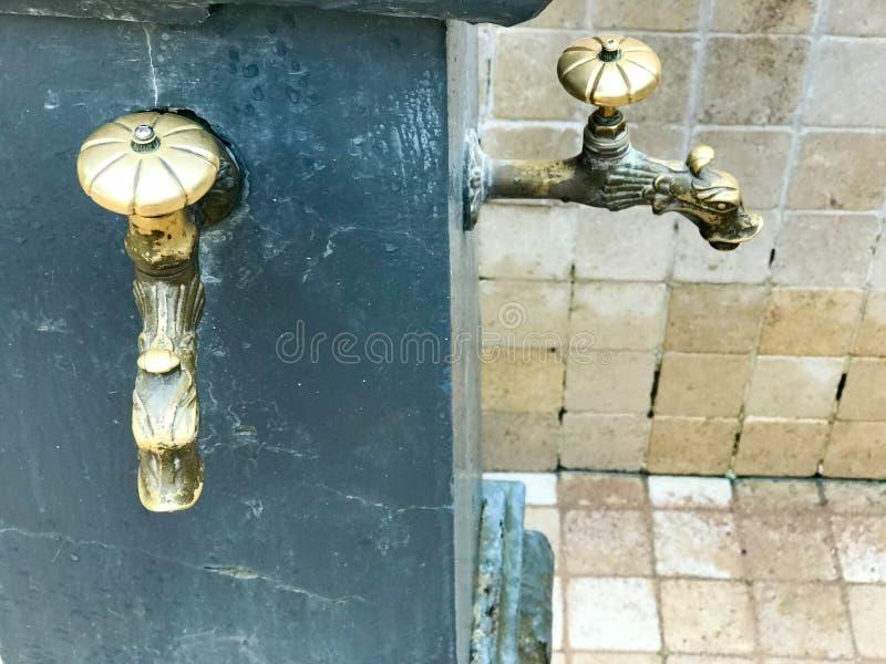 Het zwarte ijzer sneed gesmede fontein met twee mooie geweven tapkranen, kleppen, messingsmontage, koper voor het drinken, wassen stock foto