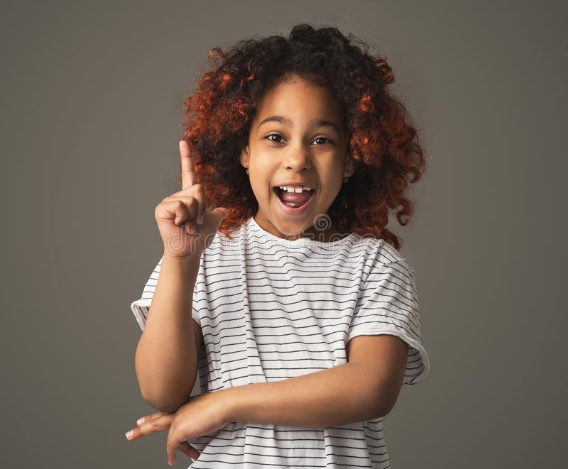Het zwarte jong geitjemeisje heeft idee, die vinger op gebaar maken royalty-vrije stock foto