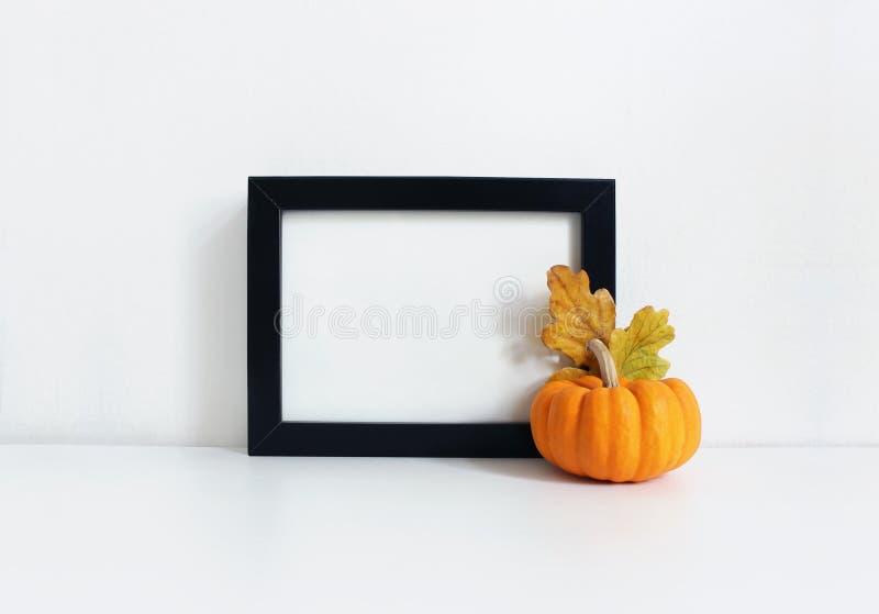 Het zwarte lege houten kadermodel met een oranje pompoen en een gouden eik verlaat het liggen op de witte lijst Afficheproduct royalty-vrije stock fotografie