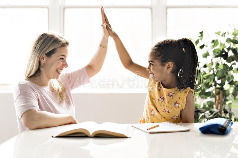 Het Zwarte meisje die van de moederhulp thuiswerk thuis doen stock afbeelding