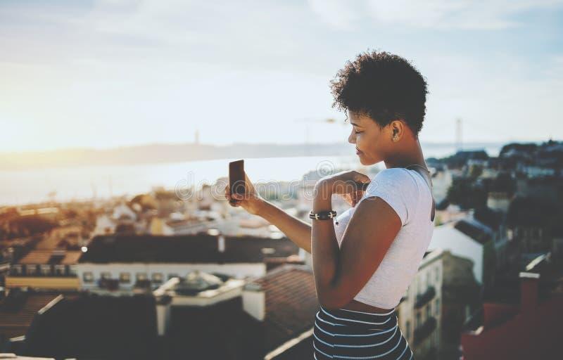 Het zwarte meisje maakt selfie met cityscape op achtergrond stock fotografie