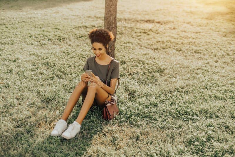 Het zwarte meisje zit op het gras met smartphone royalty-vrije stock afbeeldingen