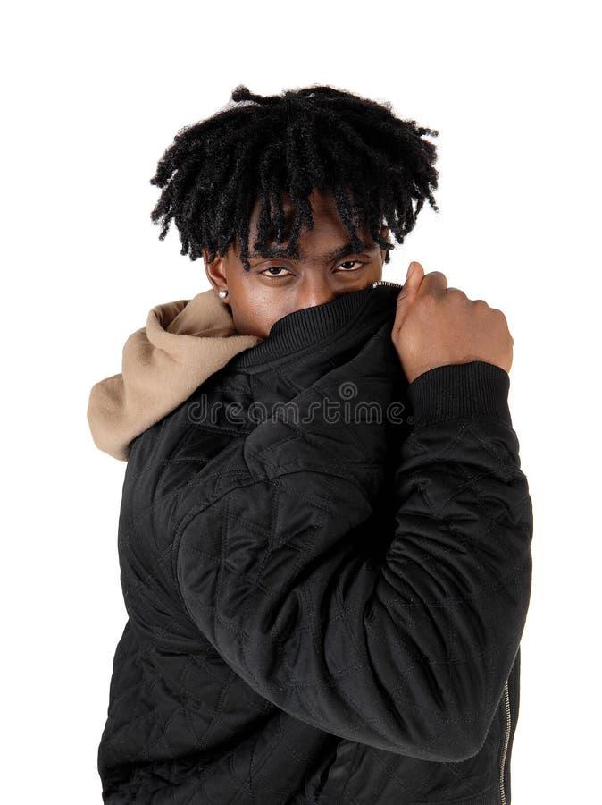 Het zwarte mens verbergen achter zijn jasje stock foto's