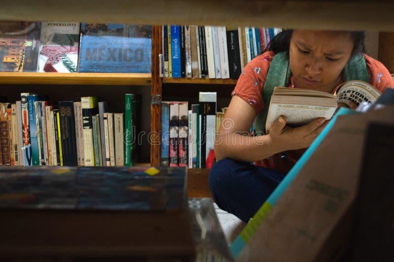 Het zwarte met boek in haar dient een bibliotheek in royalty-vrije stock afbeeldingen