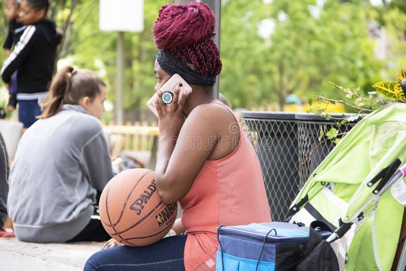 Het zwarte met rode vlechten zit op de het Verzamelen zich Plaats die een basketbal houden en op een roze telefoon spreken stock foto