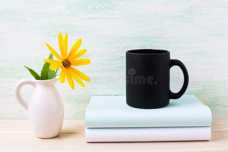 Het zwarte model van de koffiemok met geel rosinweed bloemen in waterkruik royalty-vrije stock foto's