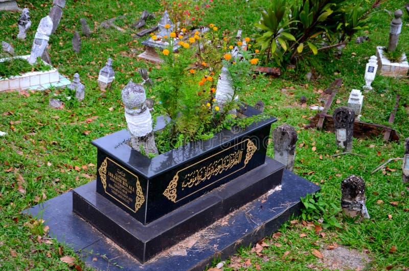 Het zwarte Moslim Maleisische graf met bloemen en Arabische Koran berijmt Kuching Sarawak Maleisië stock foto's