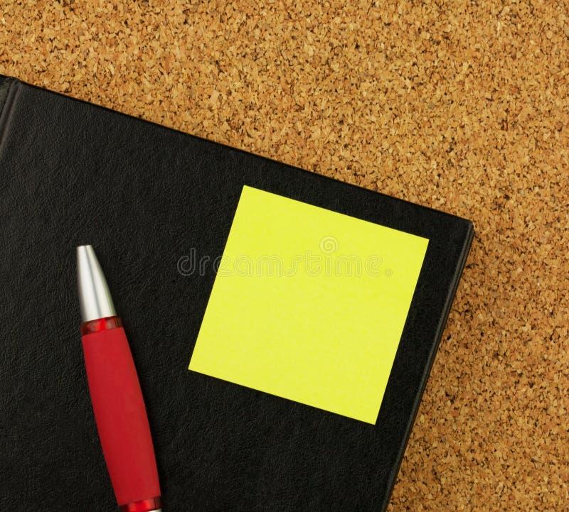 Het zwarte notitieboekje, de rode pen en de gele sticker op cork schepen achtergrond in royalty-vrije stock foto's