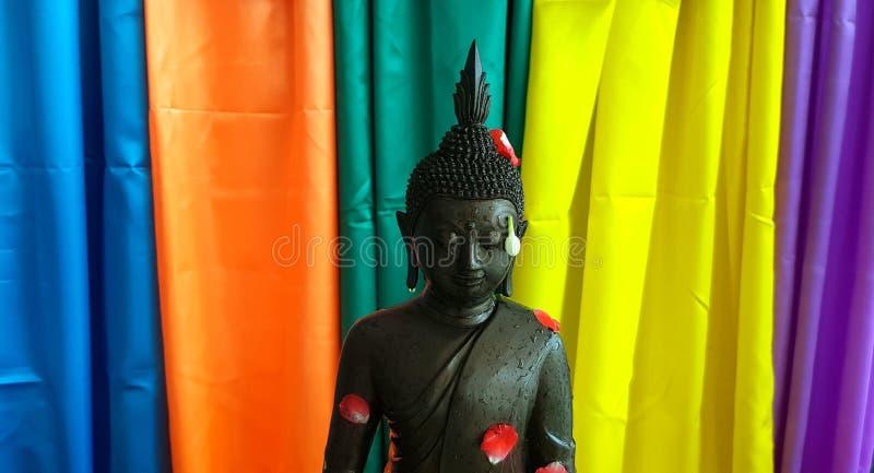 Het zwarte standbeeld van Boedha met rood bloemblaadje nam, Jasmijn op kleurrijke gordijnachtergrond toe royalty-vrije stock foto's