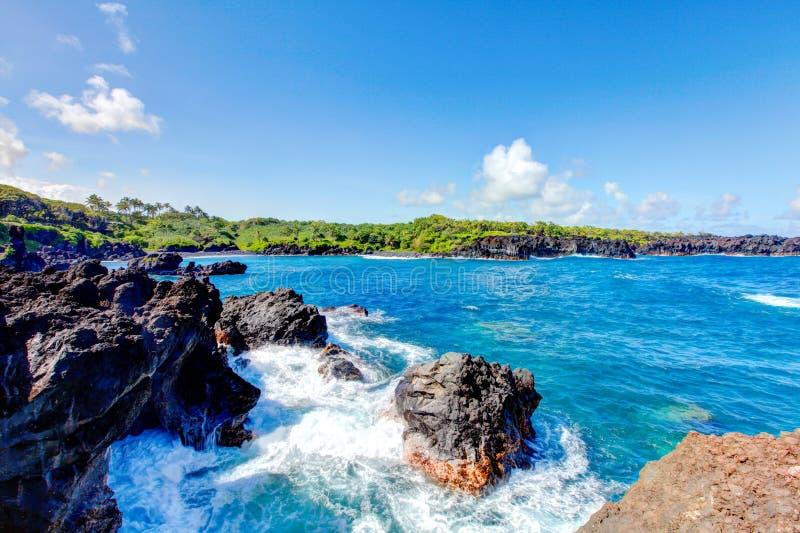 Het zwarte strand van de lavarots, weg aan Hana, Maui stock foto