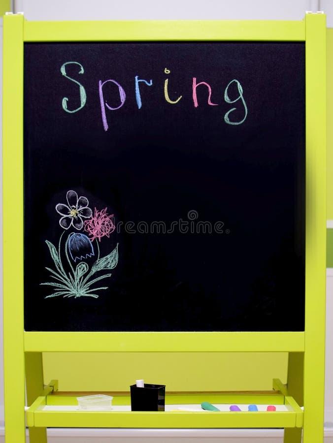 Het zwarte studentenschoolbord met een tribune voor krijt en multi-colored inschrijving springen op stock fotografie
