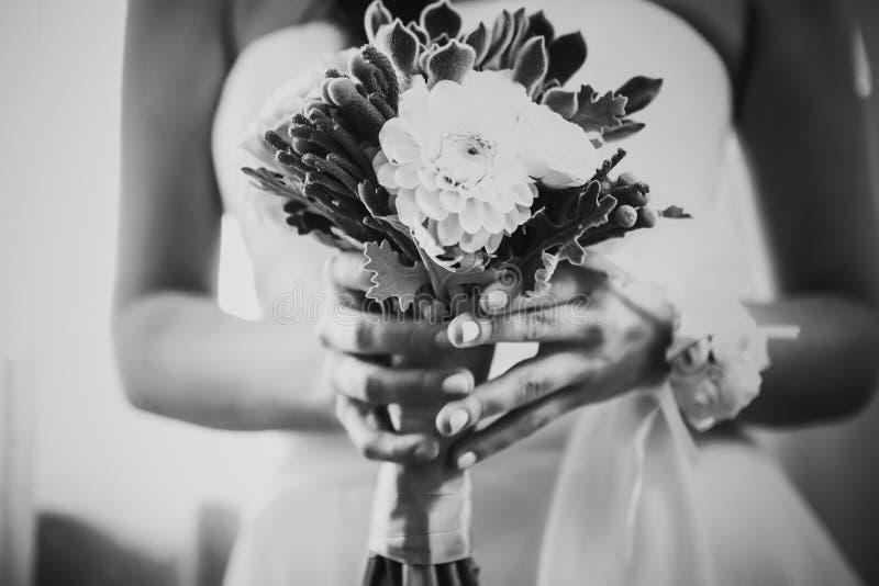 Het zwarte witte boeket van het fotografie mooie huwelijk van bloemen in handen de bruid royalty-vrije stock foto's