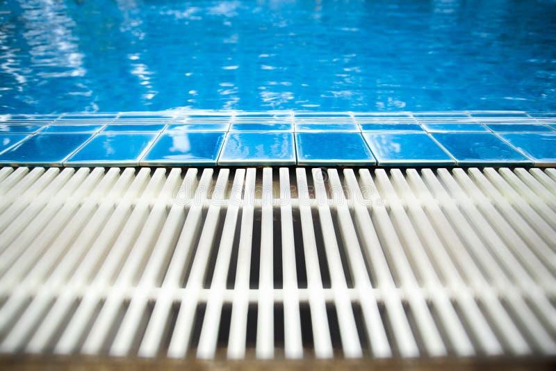 Het zwembad het beeld nam uit de rand van zwembad die door blauwe tegels en gootdrainage verstrekt Kan gebruik zijn als backg stock foto