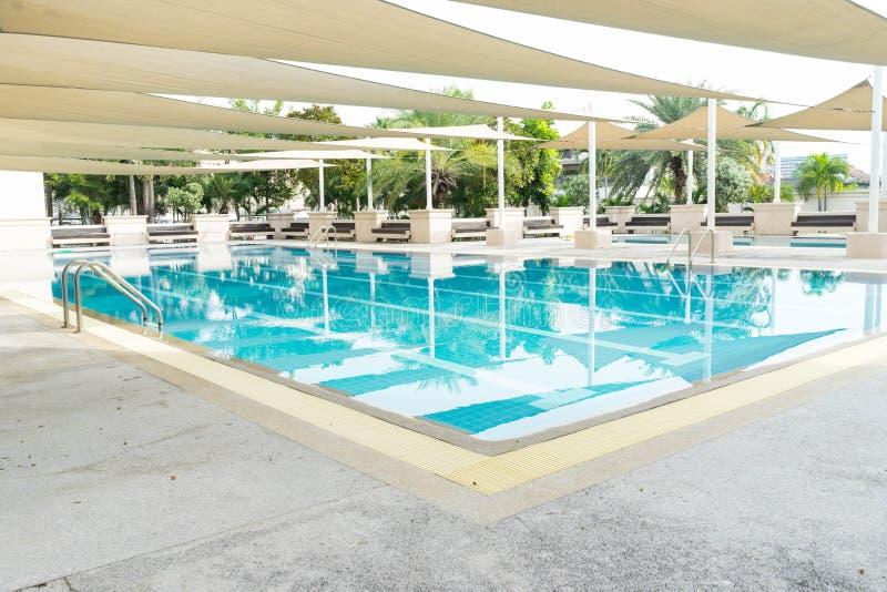Het zwembad met openlucht met zonneschermdekking voelt comfortabel stock afbeeldingen