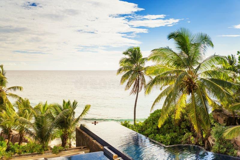 Het zwembad van de luxeoneindigheid, door palmen wordt omringd die en fron royalty-vrije stock fotografie
