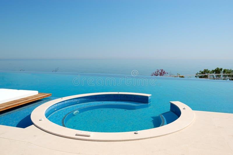 Het zwembad van de oneindigheid met Jacuzzi door strand stock afbeeldingen