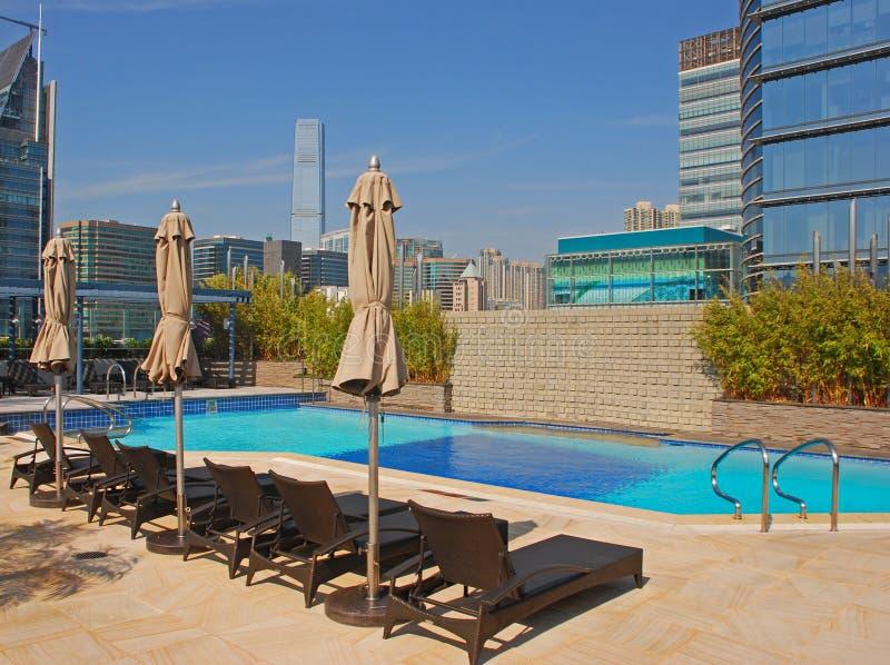 Het Zwembad van het hoteldak met deckchair & Gebouwen stock foto