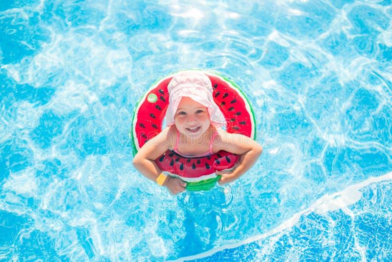 Het zwemmen, de zomervakantie - mooi glimlachend meisje in het roze hoed spelen in blauw water met reddingsboei-watermeloen stock afbeeldingen