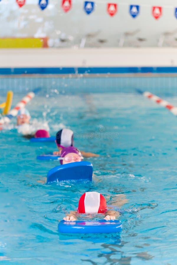 Het zwemmen Jonge geitjesles met zwemmende lijst op een rij stock foto