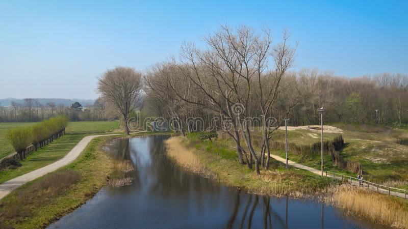 Het Zwin自然保护、平静的河、森林和一条小路走的,Knokke,比利时 免版税库存照片