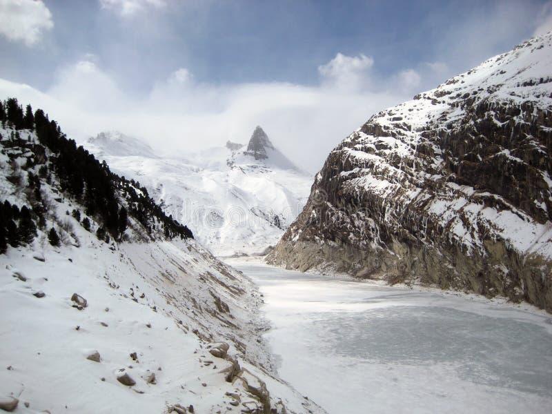 Het Zwitserse meer van Zervreilahorn en van de barrière in de winter stock afbeeldingen