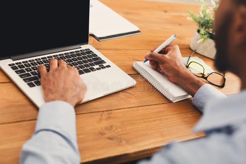 HetAmerikaanse zakenman typen op laptop stock afbeeldingen