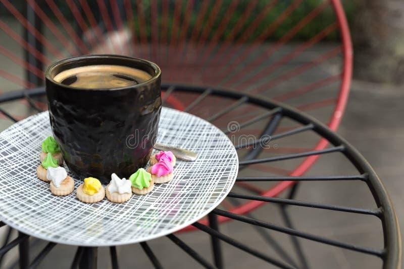 Hete Americano-koffie met cremabovenkant in een elegant zwart glas surr stock afbeeldingen