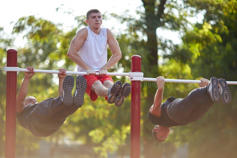 Hete bodybuilder die opdrukoefeningen op een parkachtergrond doen Openbaar sportuitrustingconcept royalty-vrije stock foto's